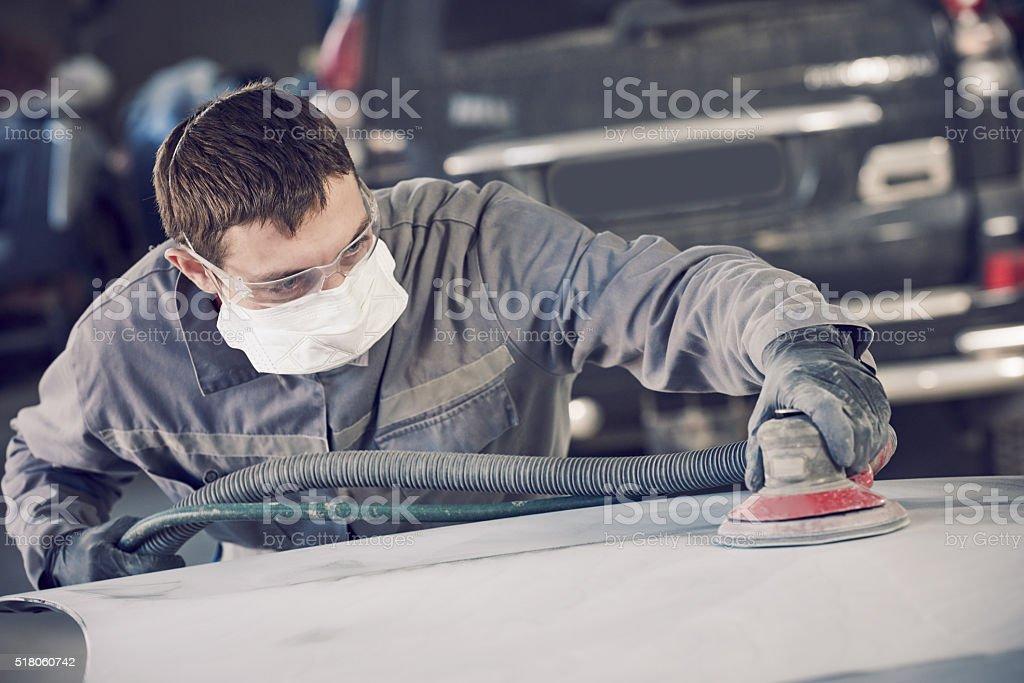 auto repairman grinding autobody bonnet stock photo