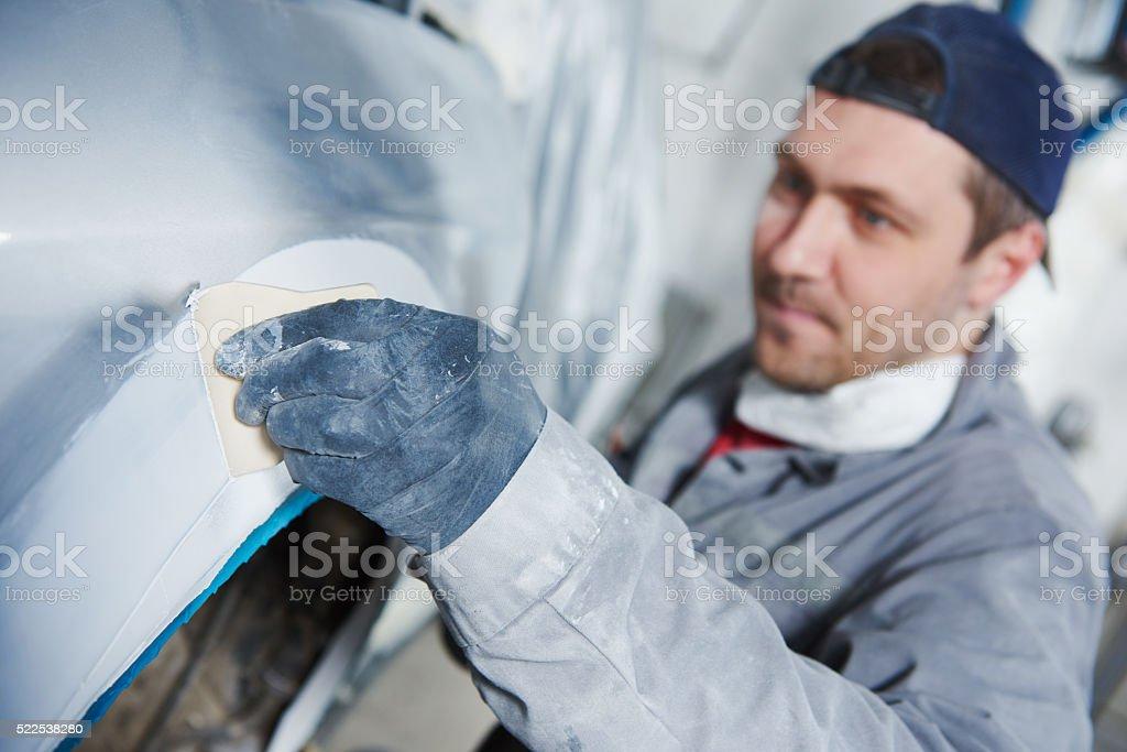 auto repairman plastering autobody bonnet stock photo