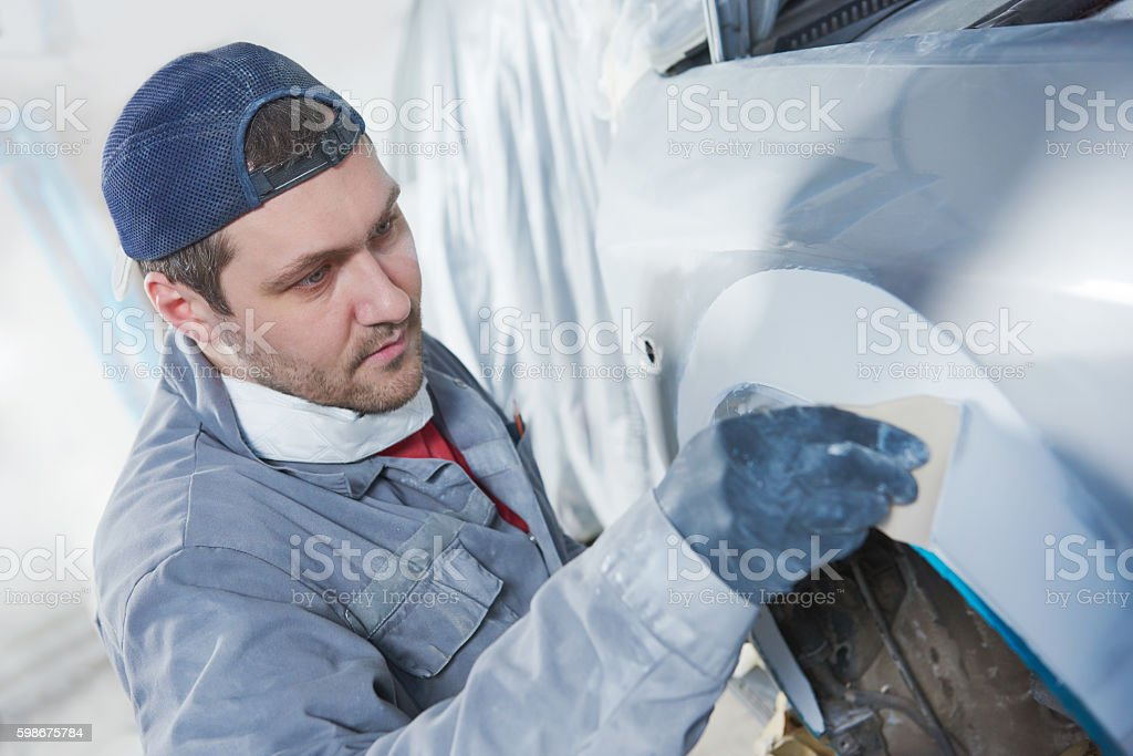 auto repairman plastering autobody bonnet stock photo