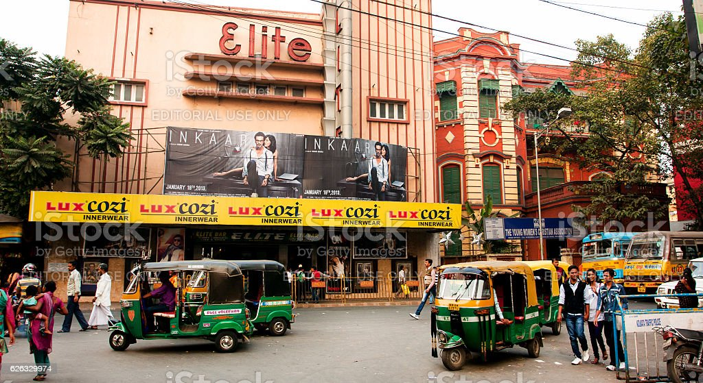 Auto rickshaw taxis move past the cinema theater. India stock photo