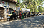 Cherthala, Kerala,India - January 15, 2013: Row of auto rickshaws along the street in the town of Cherthala, a location in the Alappuzho district of Kerala, about 30 km south of Kochi. Drivers are standing near the rickshaw and two ladies in traditional dress are passing by.