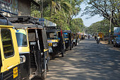 Cherthala, Kerala,India - January 15, 2013: Row of auto rickshaws along the street in the town of Cherthala, a location in the Alappuzho district of Kerala, about 30 km south of Kochi. Drivers are standing near the rickshaw and some motorbikes on the street.