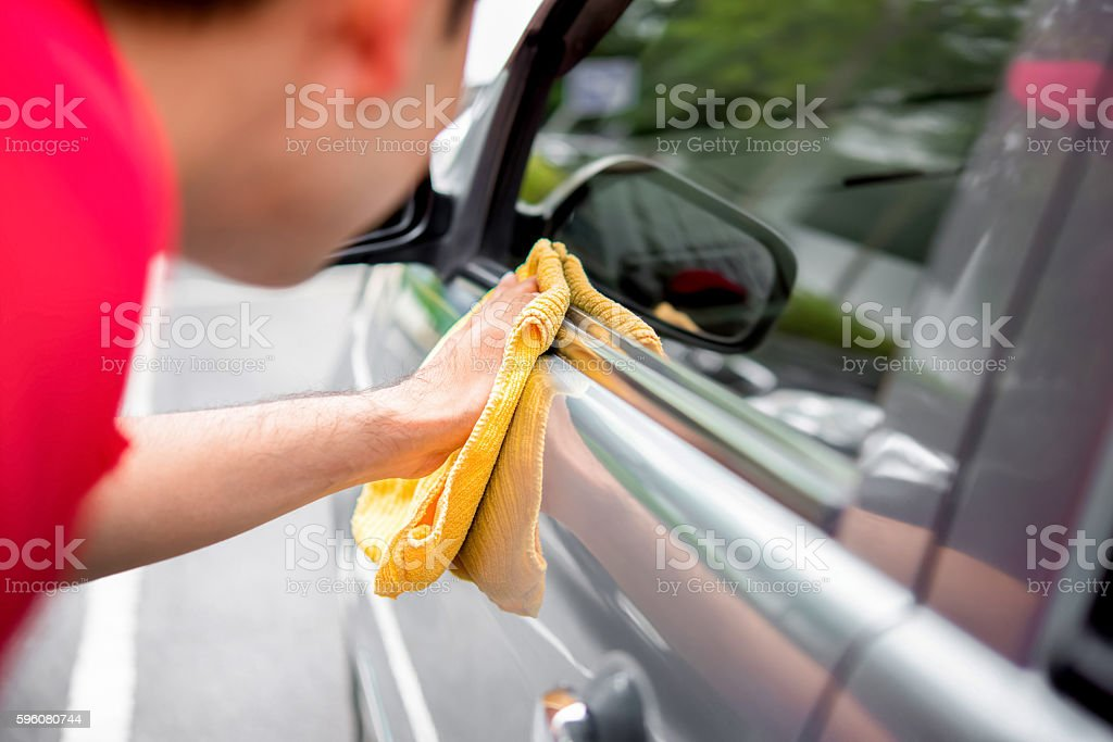 Auto service staff cleaning car with microfiber cloth stock photo