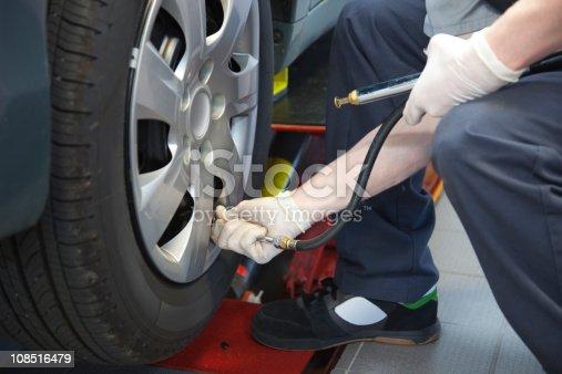 898487280 istock photo Auto Service Technician Checking Tire Pressure 108516479
