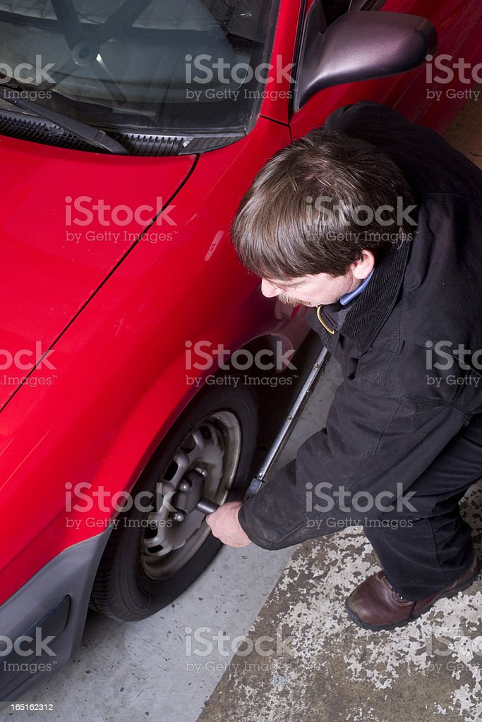 Auto Technician Uses Breaker Bar Loosening Lug Nuts on Car stock photo