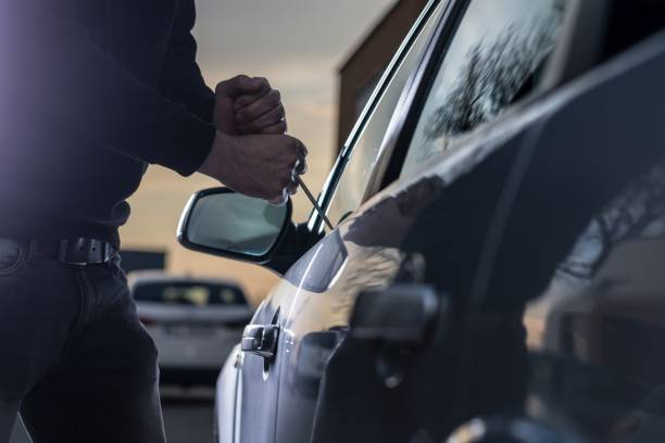 auto thief in black balaclava trying to break into car - thief stock photos and pictures