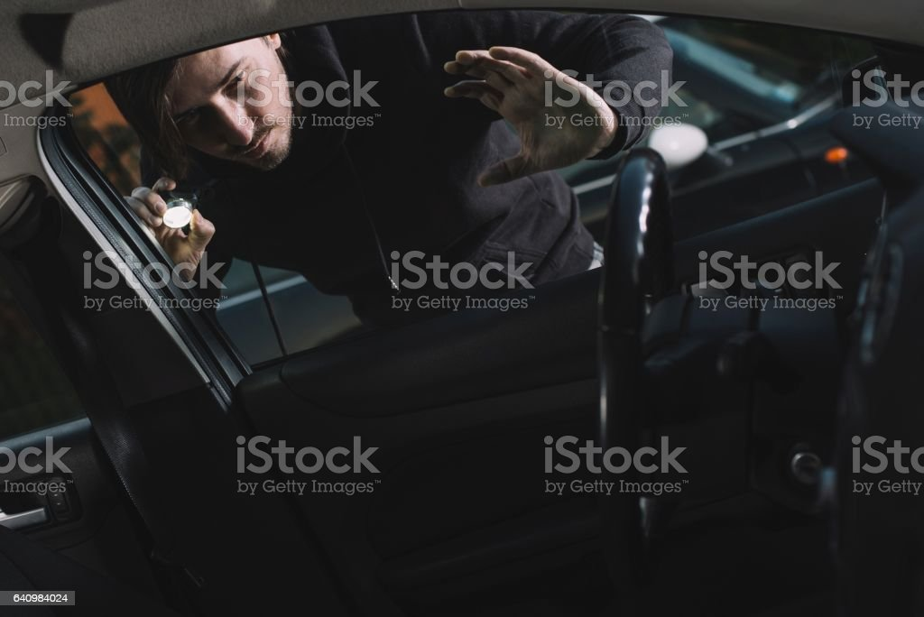 Auto thief looking to car interior stock photo