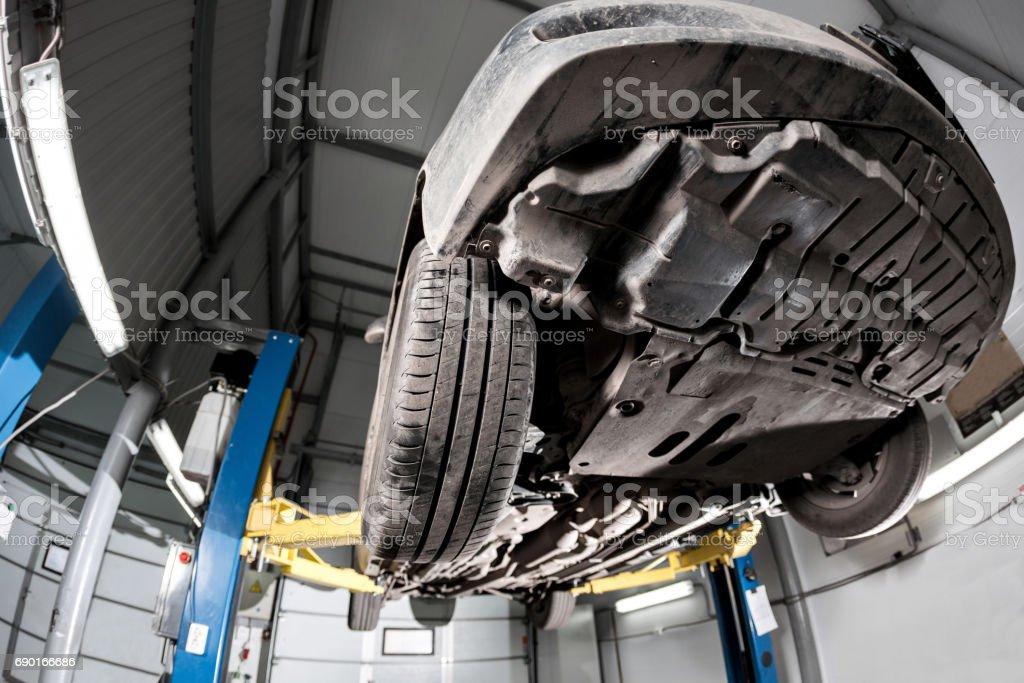 Auto de vista de la parte inferior. suspensión delantera del coche. el mecánico del garage levantado el coche en el elevador - foto de stock