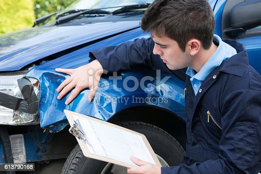 istock Auto Workshop Mechanic Inspecting Car And Filling In Repair Estimate 613790168