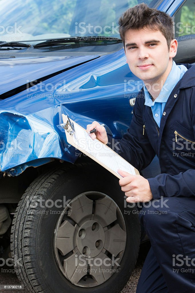 Auto Workshop Mechanic Inspecting Car And Filling In Repair Estimate stock photo