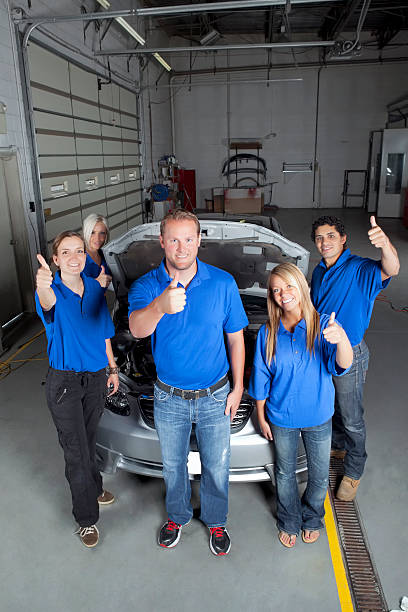 autobody shop with happy employees, job well done thumbs up stock photo