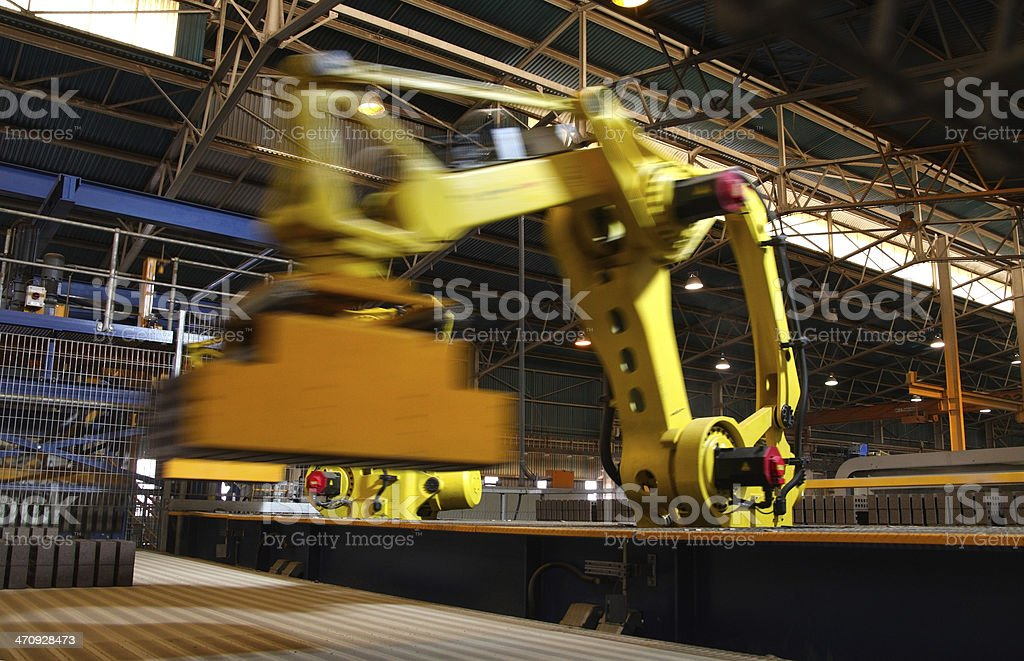 Automated production line handling robots picking up goods, fast motion. stock photo