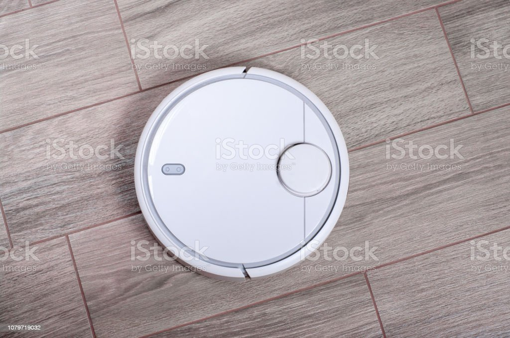 automated robot vacuum cleaner on tile floor. smart robotic automate wireless cleaning technology housekeeping stock photo