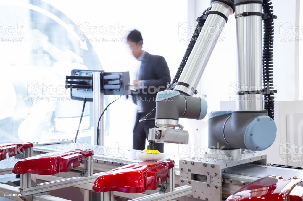 Automated robotic arm polishing automotive part in production line...