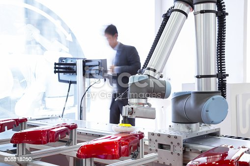 istock Automated robotic arm polishing automotive part in production line factory 808818250