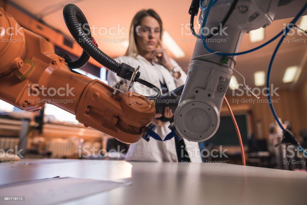 Braços robóticos automatizados em laboratório com o engenheiro em segundo plano. - foto de acervo