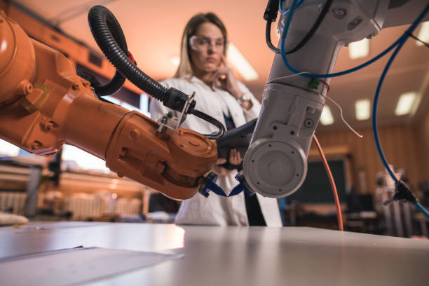 Automated robotic arms in laboratory with engineer in the background. stock photo