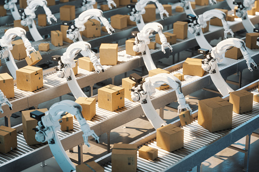 Automated factory with robotic arms carrying boxes.