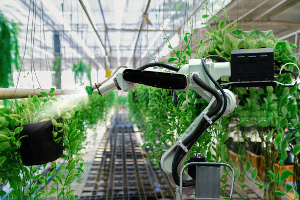 Automatic agricultural technology robot arm watering plants tree stock photo