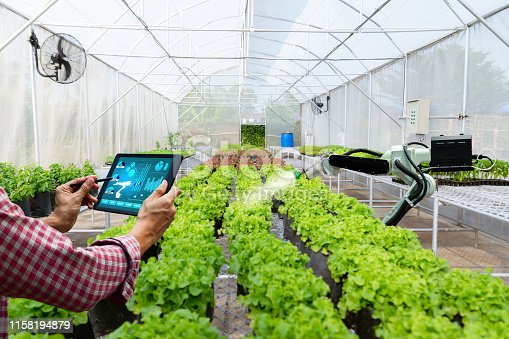 istock Automatic agricultural technology robot arm watering plants tree 1158194879