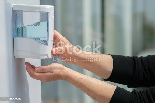 Famale patient hands using automatic alcohol dispenser for cleaning hand in the hospital. Infection prevention concept. Save and clean in public medical center area.