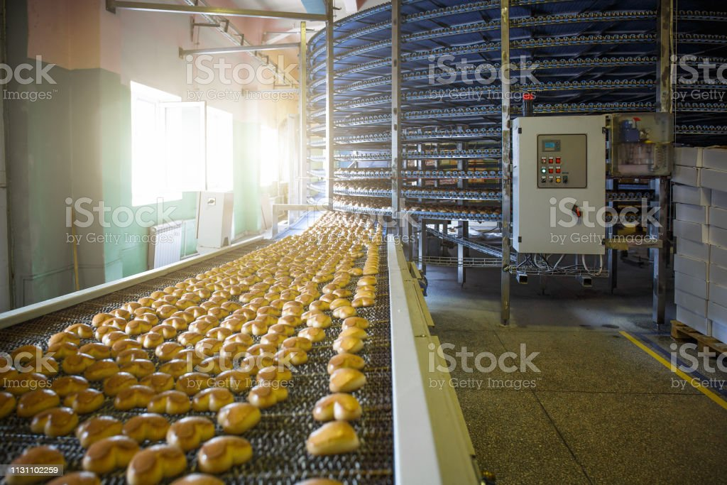 Automatic bakery production line with sweet cookies on conveyor belt...