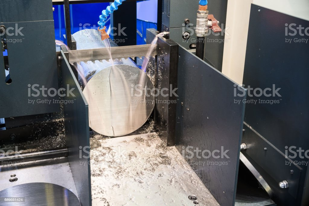 Automatic bandsaw sawing metal workpiece stock photo