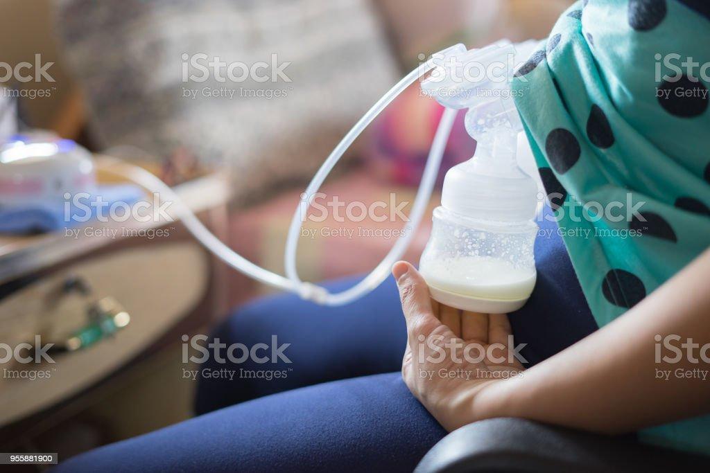 Bomba automática, leite de mães seios é o alimento mais saudável para o bebê recém-nascido. Mãe feliz com babys no quarto de cama, casa, vintage cor - foto de acervo