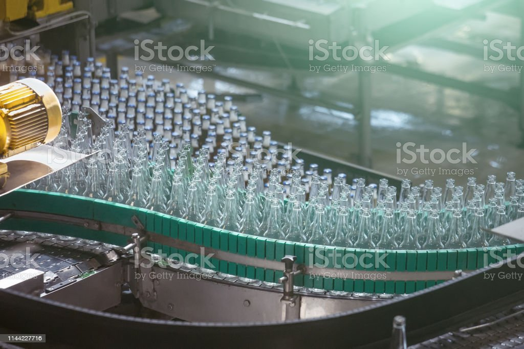 Automatic conveyor line or belt with glass bottles at brewery...