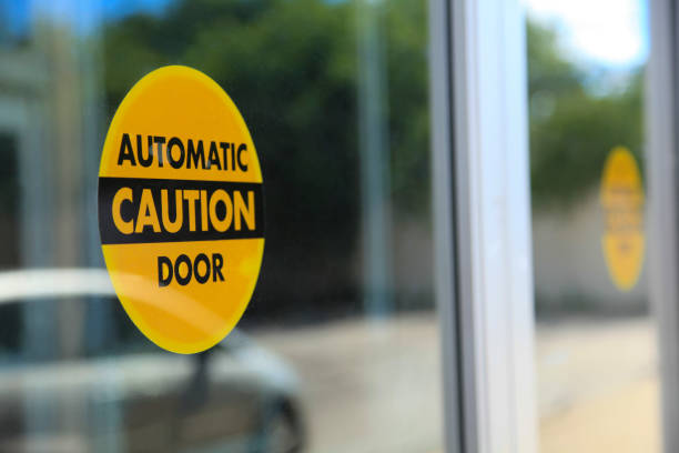Automatic Door Caution Sign Automatic door caution stickers attached to a store glass doors. automatic stock pictures, royalty-free photos & images