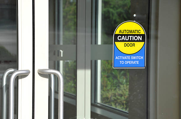 Automatic door with caution sign stock photo