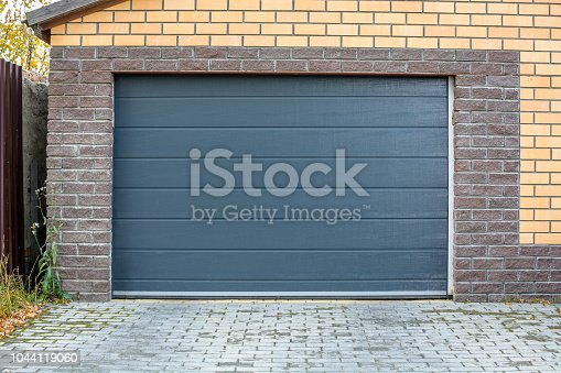 istock Automatic garage gate. Access to a brick garage for a car with a dark door 1044119060