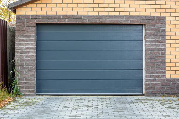 automatische garage tor. zugang zu einer gemauerten garage für ein auto mit einer dunklen tür - fassadenschnitt stock-fotos und bilder