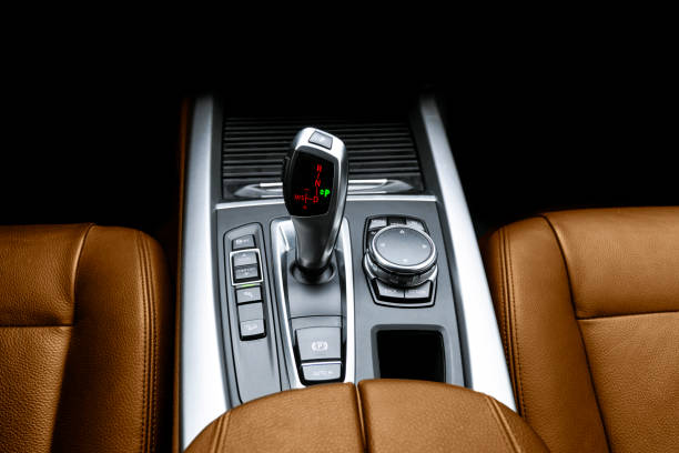 Automatic gear stick (transmission) of a modern car. Multimedia and navigation control buttons. Car interior details. Transmission shift. Brown leather interior stock photo