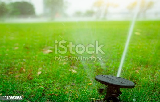 istock Automatic lawn sprinkler watering green grass. Garden, yard irrigation system watering lawn. Water saving or conservation from sprinkler system. Turf farm business. Sprinkler service and maintenance. 1212663986
