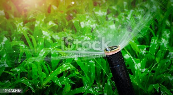 istock Automatic lawn sprinkler watering green grass. Sprinkler with automatic system. Garden irrigation system watering lawn. Water saving or water conservation from sprinkler system with adjustable head. 1049233484