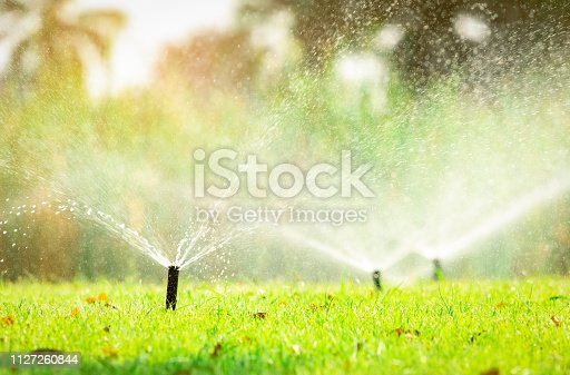 istock Automatic lawn sprinkler watering green grass. Sprinkler with automatic system. Garden irrigation system watering lawn. Sprinkler system maintenance service. Home service irrigation sprinkler. 1127260844
