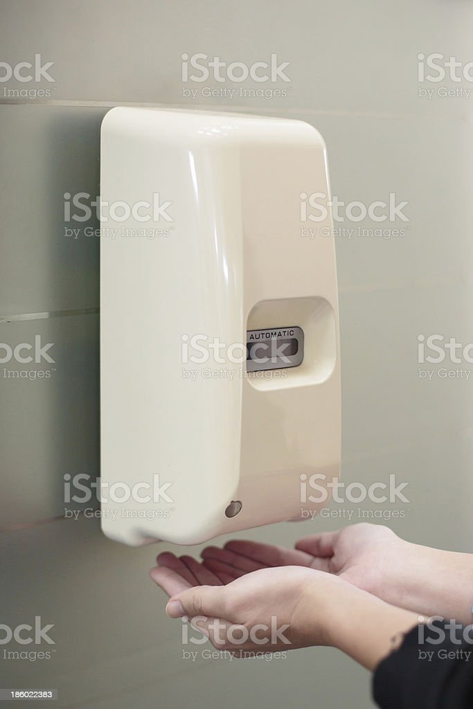 Automatic liquid soap dispenser on wall stock photo