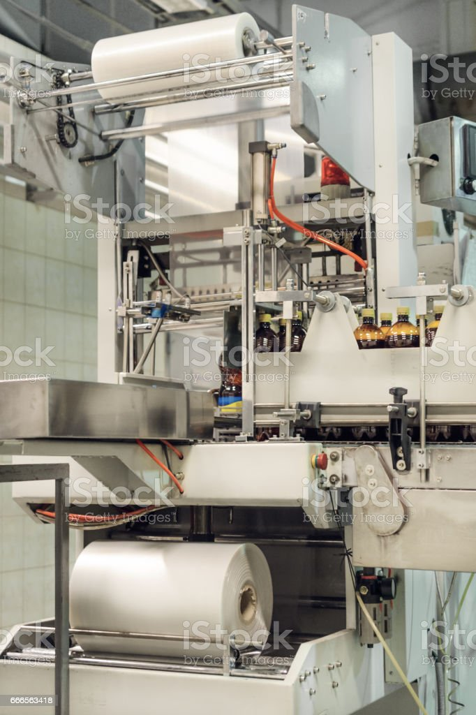 Automatic packaging machine packs bottles stock photo
