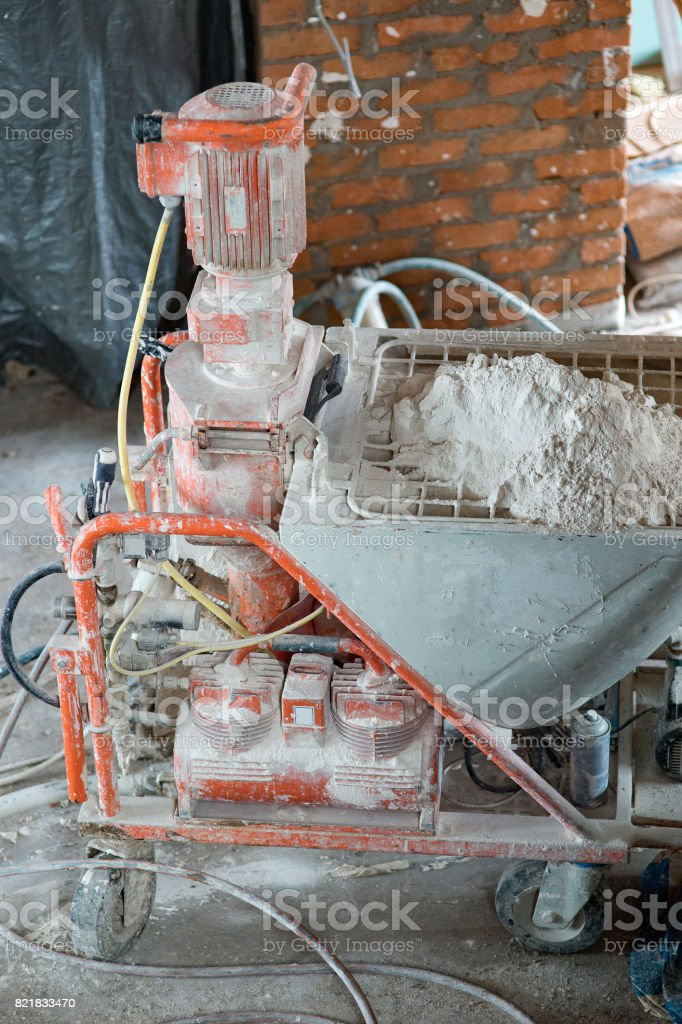 Automatic Spray Plastering Machine for Plastering Walls efficiently on Building of an apartment house stock photo