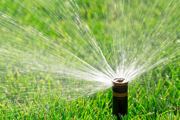 Automatic sprinkler automatic sprinkler watering fresh lawn irrigation equipment stock pictures, royalty-free photos & images
