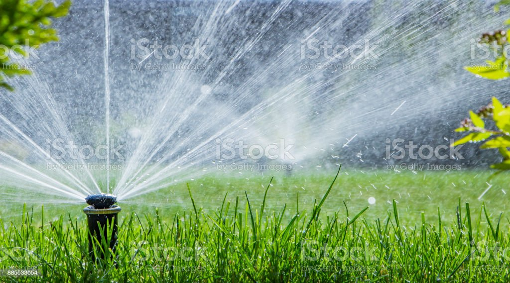 automatic sprinkler system watering the lawn on a background of green grass stock photo