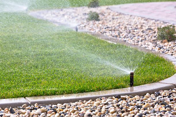 Automatic sprinklers Automatic sprinklers watering grass irrigation equipment stock pictures, royalty-free photos & images