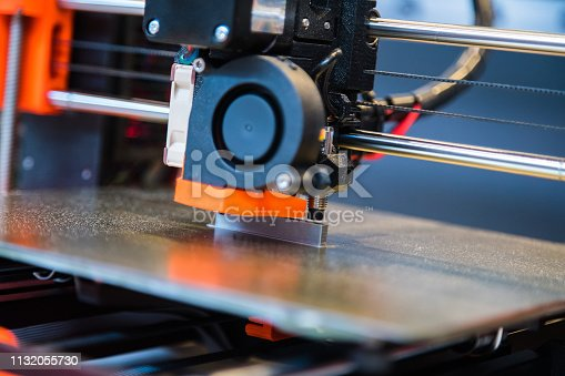 istock Automatic three dimensional 3d printer performs product creation. Modern 3D printing or additive manufacturing and robotic automation technology 1132055730