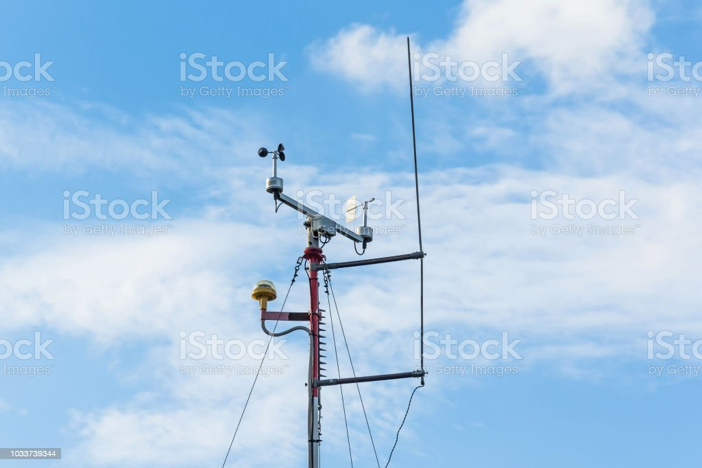 Automatic weather station, with a weather monitoring system. Against the background of a blue sky with clouds. - foto stock