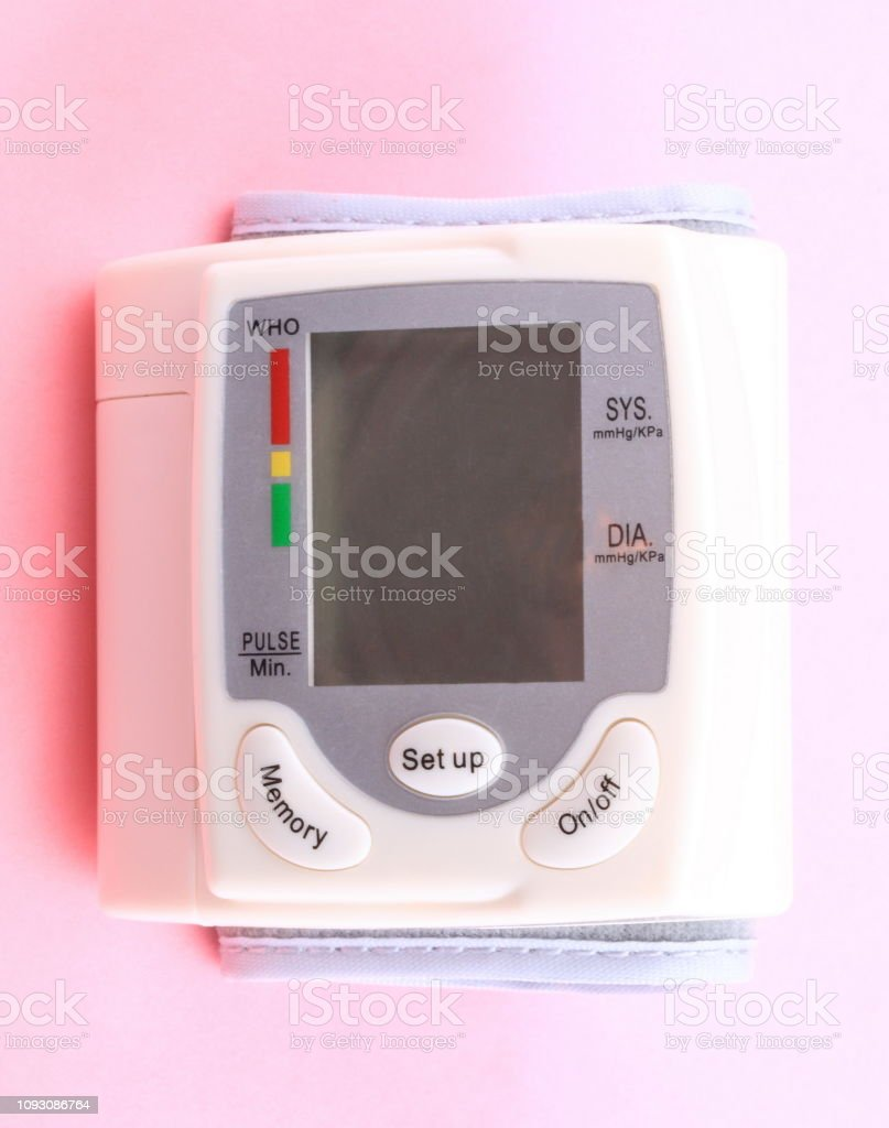 Automatic Wrist Digital blood pressure monitor on pink background at dry day stock photo