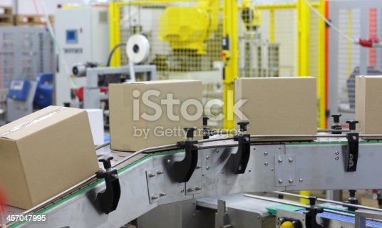 istock automation - Cardboard boxes on conveyor belt in factory 457047995