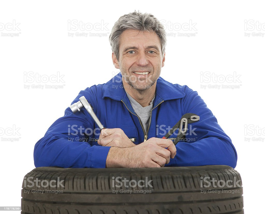 Automechanic leaning on car tires royalty-free stock photo