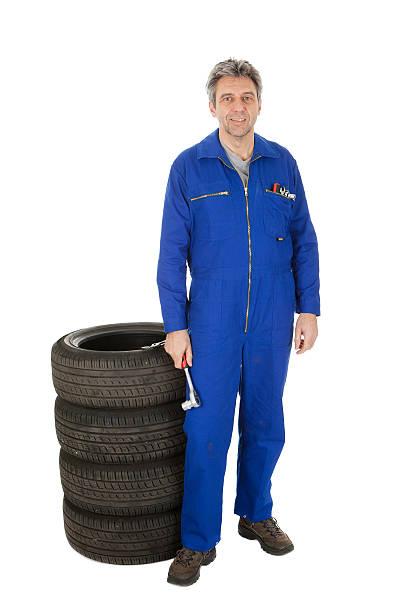 automechanic stehen neben dem auto reifen - jumpsuit blau stock-fotos und bilder