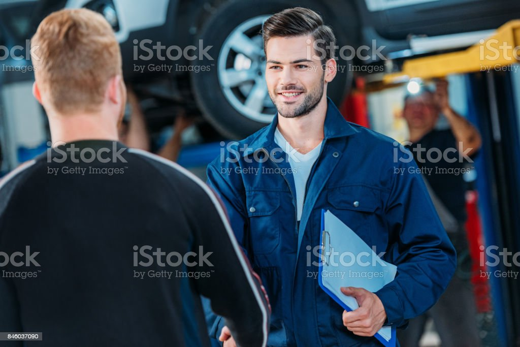 Automechanic welcoming client stock photo